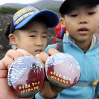 Boys show off the badges given to those who fork out the payment. | KYODO