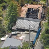 Mean street: The home of murder/arson suspect Kosei Homi is blocked off with tarp Friday in Shunan, Yamaguchi Prefecture. Also shown is the gutted house of Miyako Yamamoto, one of five elderly neighbors slain earlier this week. | KYODO