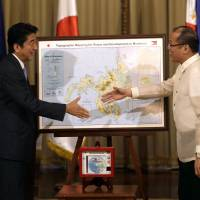 Working together: Prime Minister Shinzo Abe and Philippine President Benigno Aquino III shake hands after Abe presented him with a map showing development efforts on the island of Mindanao at the conclusion of their joint news conference Saturday in Manila. | AP