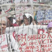 Looking for recognition: Filipino women who say they were forced into sexual slavery during the war hold a rally behind barbed wire outside the Malacanang presidential palace in Manila on Saturday.   AP