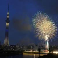 Brief bang: Fireworks light up the sky Saturday along the Sumida River in Tokyo before it was canceled by a thunderstorm.   KYODO