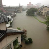 High water: Houses and roads in the city of Yamaguchi are flooded following heavy rainfall on Sunday morning.   KYODO