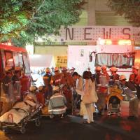 Bad reaction: Women who started feeling sick during an outdoor concert by the pop group NEWS are taken to the hospital in Tokyo's Aoyama district late Saturday night after the show was halted by rain. | KYODO