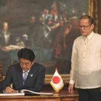 For the record: Philippine President Benigno Aquino (right) watches Prime Minister Shinzo Abe sign the guest book before their meeting at Malacanang Palace in Manila on Saturday. | AFP-JIJI/MALACANANG PHOTO BUREAU