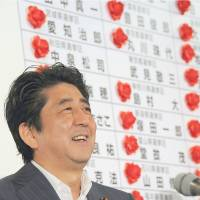 Looks tell it all: Liberal Democratic Party President Shinzo Abe smiles at LDP headquarters, while Democratic Party of Japan President Banri Kaieda frowns as they learn the results of the July 21 Upper House poll. | SATOKO KAWASAKI, YOSHIAKI MIURA