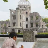 Drawn in: A local elementary school boy sketches the A-Bomb Dome in Hiroshima Peace Memorial Park on Saturday. | KYODO