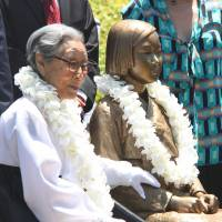 Etched in memory: Kim Bok-dong, 87, who spent eight years as a 'comfort women' for the Imperial Japanese Army, sits next to a bronze statue dedicated to the wartime sex slaves at Glendale Central Park near Los Angeles on Tuesday during the memorial's unveiling. | KYODO