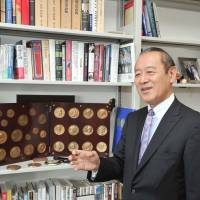 Newly minted: Ichiro Fujisaki, new president of the America-Japan Society, Inc. and former ambassador to the U.S., speaks to The Japan Times in front of his collection of commemorative coins of U.S. presidents on July 11. | YOSHIAKI MIURA
