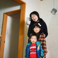 Still standing: Naoko Nakayama poses with her two children at their tsunami-damaged house in Ishinomaki, Miyagi Prefecture, before the house was reconstructed. | COURTESY OF THE NAKAYAMA FAMILY