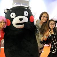 Grin and bear it: Participants of Japan Expo pose for photos with Kumamon, the official bear mascot of Kumamoto Prefecture, at the convention in Paris on Thursday.    | KYODO