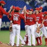 Good job, good effort: The Carp celebrate after a 3-2 win over the Dragons on Wednesday. | KYODO