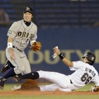 Going the extra mile: Orix's Ryoichi Adachi, left, attempts to turn a double play after Lotte's Yoshifumi Okada is forced out at second on Wednesday. The Buffaloes won 4-3. | KYODO