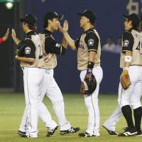 A show of hands: The Hokkaido Nippon Ham Fighters exchange high-fives after a 9-5 road victory over the Chiba Lotte Marines on Tuesday. | KYODO