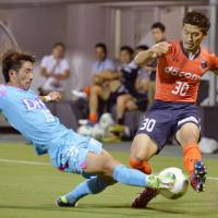 Back in action: Sagan Tosu's Ryuhei Niwa (left) and Omiya Ardija's Daisuke Watabe vie for the ball in Saturday's J.League match in Saitama. The teams settled for a 1-1 draw as the J.League resumed play after a six-week international break. | KYODO