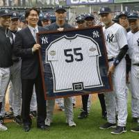 True Yankee: Hideki Matsui, left, and Yankees captain Derek Jeter hold a framed Matsui jersey while surrounded by members of the Yankees on Sunday in New York. | KYODO