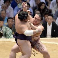 Firm footing: Kisenosato (right) grapples with Takekaze on the opening day of the Nagoya Grand Sumo Tournament on Sunday. | KYODO