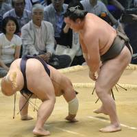No surprise: Yokozuna Hakuho (right) overpowers Takefaze on the third day of the Nagoya Grand Sumo Tournament, improving to 3-0 on Tuesday. | KYODO