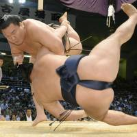 Down goes another: Yokozuna Hakuho overpowers Kakuryu on Wednesday at the Nagoya Grand Sumo Tournament, winning his 41st consecutive match. | KYODO