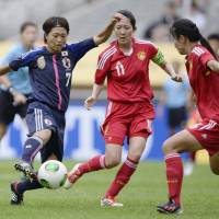 Foot skills: Japan's Kozue Ando (left) dribbles the ball against China in the Women's Asian Cup opener in Seoul on Saturday. Ando scored a goal in Japan's 2-0 triumph. | KYODO