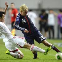 Yojiro Takahagi struggles to maintain control over the ball during the East Asian Cup opener with China Sunday in Seoul. | KYODO