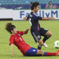 In the heat of the moment: Japan's Mana Iwabuchi (right) is tackled by South Korea's Lim Seon-joo during their Women's East Asian Cup match in Seoul on Saturday. South Korea defeated Japan 2-1. | AP