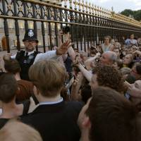 Siege at the gates: A police officer tries to control a crowd attempting to get to the fence of Buckingham Palace in London to take pictures of a public notice proclaiming the birth of a baby boy to Prince William and Catherine, Duchess of Cambridge, on Monday.   | AP