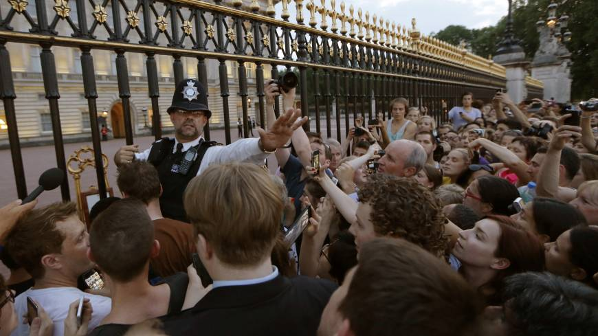 Siege at the gates: A police officer tries to control a crowd attempting to get to the fence of Buckingham Palace in London to take pictures of a public notice proclaiming the birth of a baby boy to Prince William and Catherine, Duchess of Cambridge, on Monday.     AP