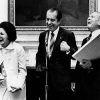 Three's a crowd: U.S. President Richard Nixon (center), Helen Thomas, then working for the United Press International news wire, and her fiance, Associated Press reporter Douglas Cornell, share a light moment during an impromptu reception in Washington in September 1971. The couple married the following month. | AP