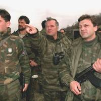 Facing justice: Bosnian Serb Army commander-in-chief Ratko Mladic (center) observes Bosnian government positions in Gorazde, eastern Bosnia, while surrounded by bodyguards in April 1994. Mladic is on trial at the U.N. war crimes tribunal in The Hague, accused of overseeing war crimes that include the slaughter of 8,000 Muslims in Srebrenica during Bosnia's 1992-95 war. | AP
