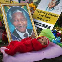 Grandfather of the nation: Four-month-old Oamohetswe Mabitsela lies beside a picture of Nelson Mandela while his mother takes a picture outside the Mediclinic Heart Hospital, where Mandela is being treated, in Pretoria on  Thursday. | AP