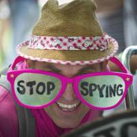 Read my eyes: An activist sports pink glasses on which the words 'stop spying' are written across the lenses during a protest against alleged privacy violations by the U.S. National Security Agency in Washington on Thursday. | AFP-JIJI
