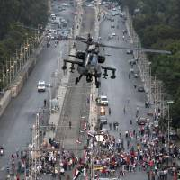 Ready to swoop: An attack helicopter flies over a street near the presidential palace in Cairo on Friday. A top Muslim Brotherhood leader, Mohammed Badie, has vowed to restore ousted President Mohammed Morsi to office, saying Egyptians will not accept 'military rule' for another day. | AP