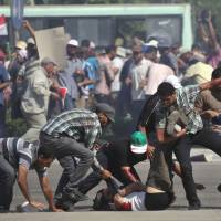 Casualty of unrest: Supporters of ousted Egyptian President Mohammed Morsi help carry a man who was shot near the Republican Guard building in Cairo on Friday. | AP