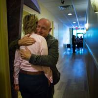 Embracing change: Retired astronaut Capt. Mark Kelly hugs his wife, former Rep. Gabrielle Giffords, before an appearance at Atomic Coffee during the Americans for Responsible Solutions tour in Fargo, North Dakota, on July 3. | THE WASHINGTON POST