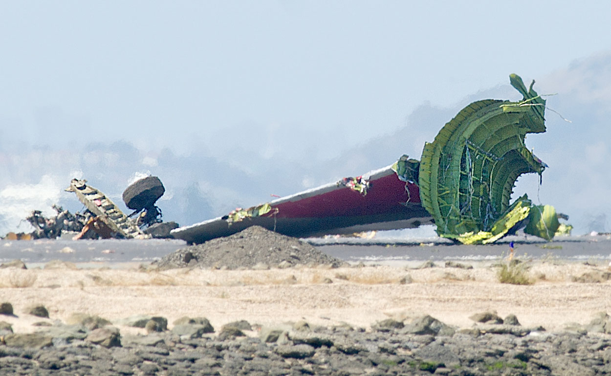 Tailing off: The detached tail and landing gear of Asiana's Boeing 777 rest on the tarmac after the plane crashed at San Francisco International Airport on Saturday. | AP