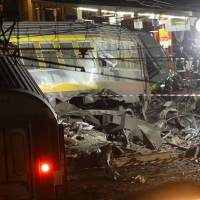 Dark day: Rescuers work at the site of a train accident at Bretigny-sur-Orge railway station, south of Paris, on Friday. | AFP-JIJI