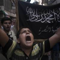 Front and center: A Syrian boy marches in front of a flag of the armed Islamic opposition group Jabhat al-Nusra during a demonstration in Aleppo in September 2012. | AP