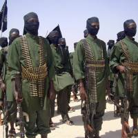 Militant stance: Al-Shabab fighters stand in formation with their weapons during military exercises on the outskirts of Mogadishu in February 2011. A handful of young Muslims from America have taken high-visibility propaganda and operational roles inside the al-Qaida-linked militant group in Somalia. | AP