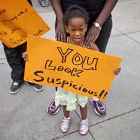 Youth message: Jediah Jones, 3, holds a sign Sunday in Atlanta as her mother, Keiota Jones, stands behind her during a protest the day after George Zimmerman was found not guilty in the 2012 shooting death of teenager Trayvon Martin.   AP