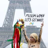 Inspirational figure: Inna Shevchenko, leader of the French branch of feminist movement Femen, holds a placard during a protest in front of the Eiffel Tower in Paris in March 2012. | AFP-JIJI