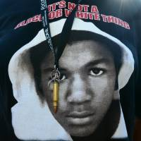 Image of power: A single bullet dangles on a ribbon over a Trayvon T-shirt being worn by a participant at a rally in Los Angeles on Monday. | AFP-JIJI
