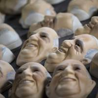 Rolling out a welcome: Pope Francis masks are dried at a factory in Sao Goncalo, Brazil, on July 9, ahead of the pontiff's visit that was to begin later Monday. Francis chose Brazil, the world's largest Roman Catholic country, for the first overseas visit of his papacy. | AP