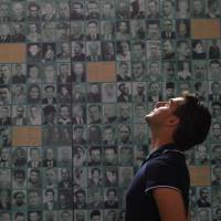 Turning back the clock: A visitor looks up while standing in front of a wall covered with photos of victims of communist repression in Sighetu Marmatiei, Romania, on July 13. | AFP-JIJI