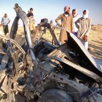 Free-fire zone: Egyptians gather Wednesday around the wreckage of a vehicle after a car bomb detonated and killed three passengers near the North Sinai town of el-Arish. Two soldiers died in separate shootings the same day in the area. | AFP-JIJI