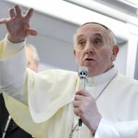 'Who am I to judge?': Pope Francis answers reporters' questions aboard the papal flight Monday on its way back from Brazil. | REUTERS/KYODO