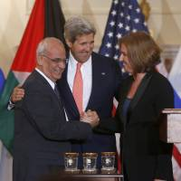 Peace talks: Secretary of State John Kerry stands between Israeli Justice Minister and chief negotiator Tzipi Livni (right) and Palestinian chief negotiator Saeb Erekat as they shake hands after the resumption of Israeli-Palestinian peace talks in Washington on Tuesday. | AP
