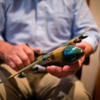 Retired U.S. Air Force Maj. Wes Carter holds a model of a C-123 cargo plane at his home in McMinnville, Oregon, last month.   THE WASHINGTON POST