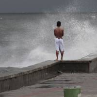 Defiant stance: A boy watches as waves strike a seawall in Navotas, north of Manila, on Monday as Typhoon Utor battered the northern Philippines. | AP