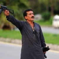Way of the gun: Mohammad Sikandar sports firearms during a standoff with police Thursday in Islamabad. | AFP-JIJI