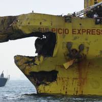 Sudden impact: A Philippine Navy boat (rear) guards a cargo ship Saturday after the ship's bow was crushed in a collision with a ferry Friday night off Cebu. | AFP-JIJI